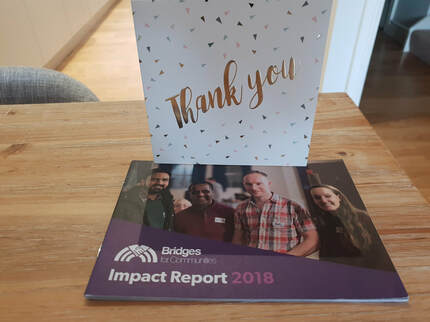 Photo of the thank you card and impact report received from Bridges for Communities