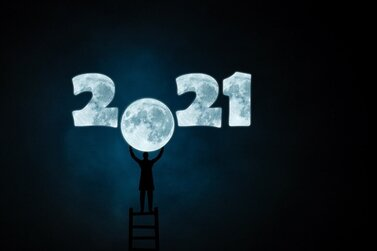 2021 sign with person holding up a moon